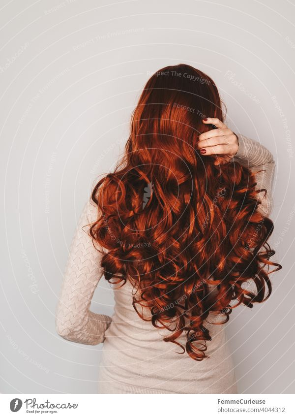 Back view of a woman with long red curly hair in a skin-colored sweater who is grabbing her hair with one hand. Neutral background Copy Space top