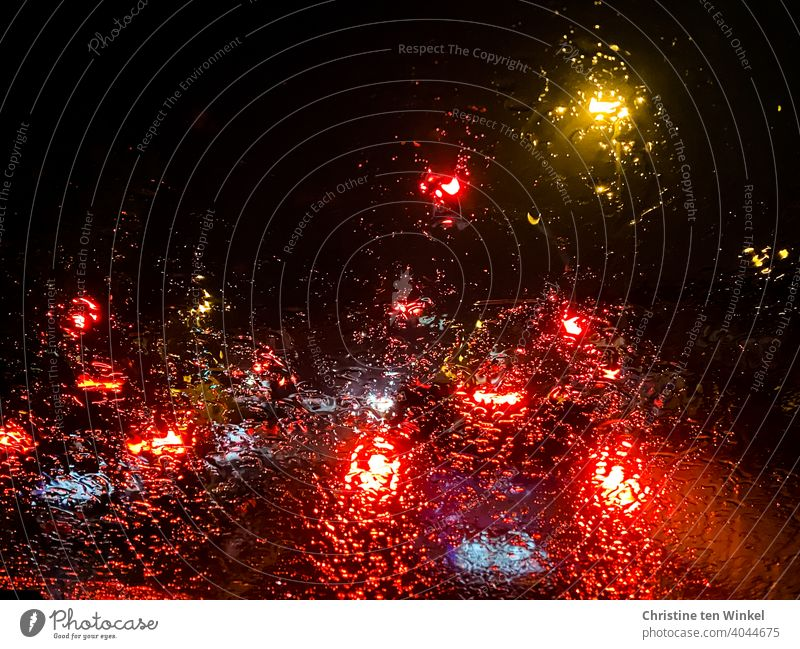 View through the rainy windscreen of a car parked at a red light in the darkness behind illuminated vehicles clearer Lights in the rain Rain Car lights Wet