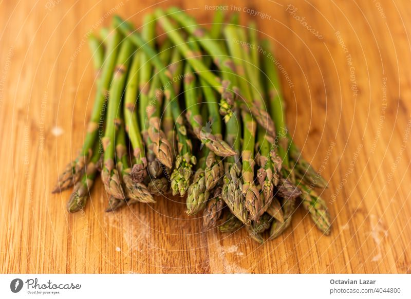 Bunch of fresh green seasonal asparagus on a wooden kitchen board close up top view shallow depth of field group bunch outside tips whole freshness preparation