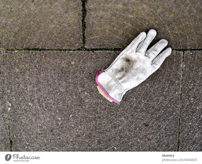 Dirty white work glove on grey stone slabs in Oerlinghausen near Bielefeld in the Teutoburg Forest in East Westphalia-Lippe finger glove White filth dirt
