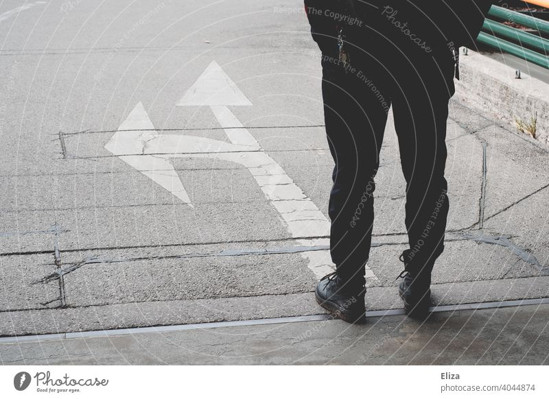 A person stands in front of arrows pointing in different directions. Decision making. Decide Arrow Direction Future decision making off Orientation Road marking