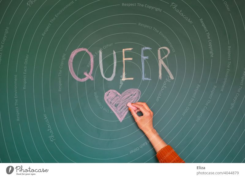 The word Queer is written in colourful letters on a blackboard. One hand draws a heart to it. queer variegated LGBTQ Tolerant Heart Love variety Equality Pride