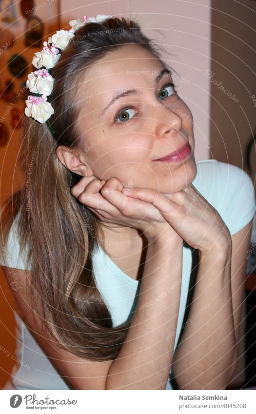 Attractive young girl in light dress and wreath with flowers on her head siting with her head propped on her hands and looking at camera close-up. Vertical orientation.