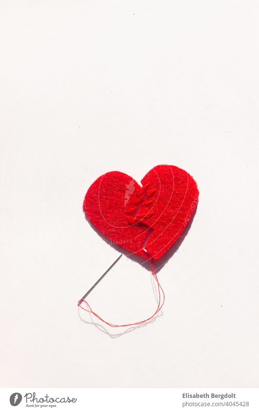 broken red heart (made of felt) on a white background, sewn back together with needle and thread. Lovesickness broken heart heartache Heart