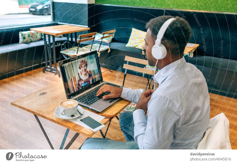 Man talking on video call with his grandmother man laptop cafe internet headphones screen person videoconference male table family sitting social distancing