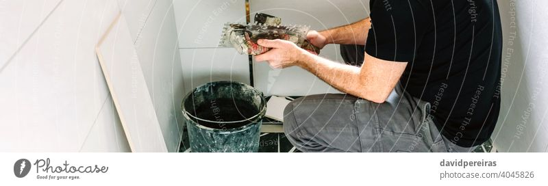 Mason working on a bathroom renovation mason crouched trowel spatula construction copy space banner web header unrecognizable panorama panoramic wall tile