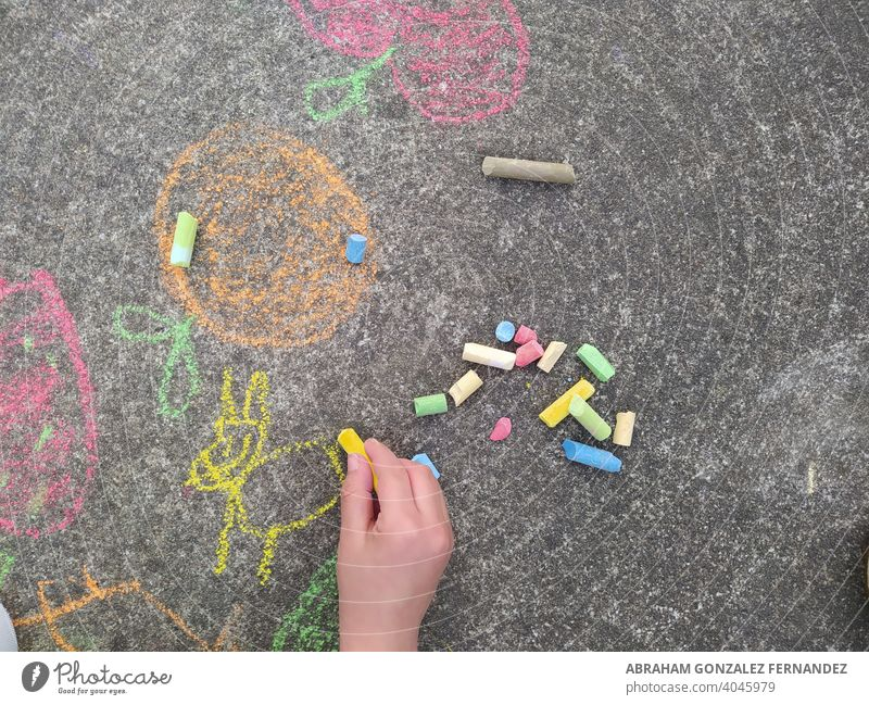 child's hand painting with colored chalk on the ground floor creativity play outside activity draw asphalt school artistic kid childhood fun playground joy