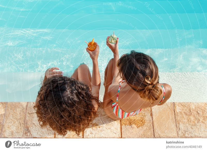 Two young women in swimsuits relaxing and drinking tropical cocktails mojito pool water Summer friends party multiethnic Together caucasian spanish Young