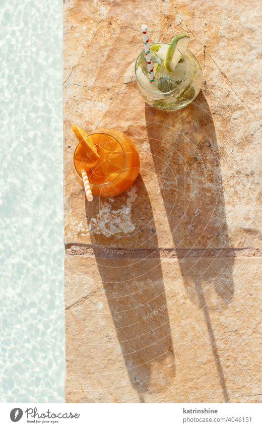 Two refreshing cocktails near a swimming pool mojito mocktail orange mint lime top view nobody glass Caipiroska caipirinha lemonade beverage drink leaf alcohol