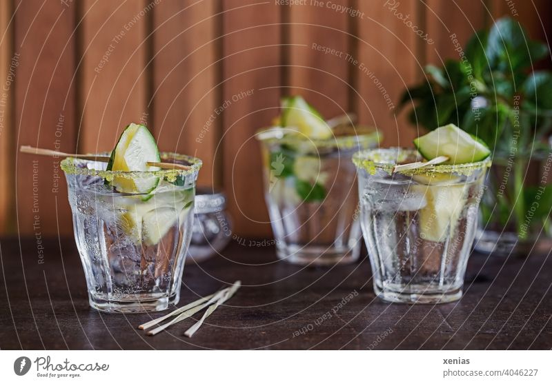 Three glasses of iced flavored water with pineapple, cucumber, peppermint and yellow sugar rim are ready to enjoy Beverage Pineapple Cold drink Water Glasses
