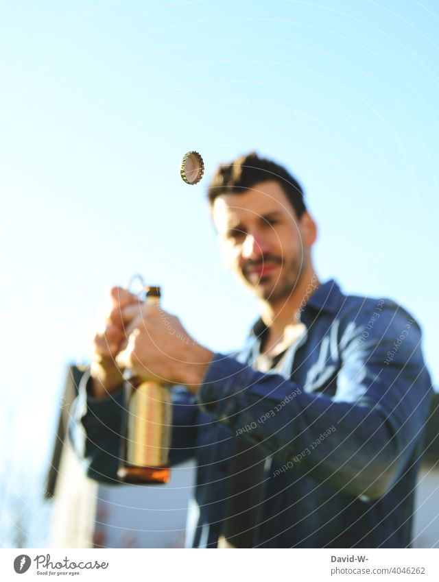 Man opens a beer bottle Beer Bottle of beer Alcoholic drinks Crown cork Flying Bottle opener good weather Summer Company Beverage Drinking Feasts & Celebrations