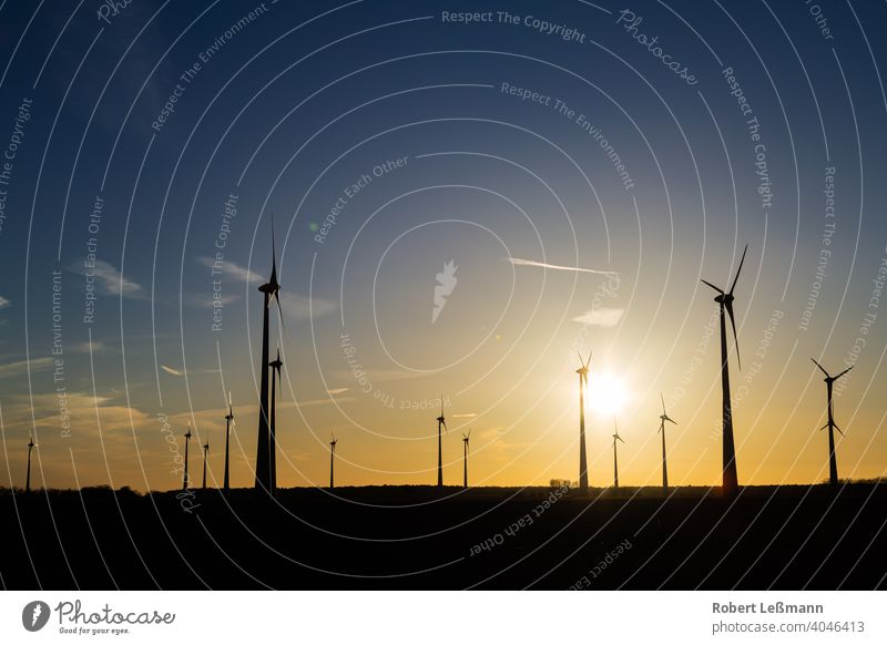 many wind turbines at sunset stand on a field and produce electricity windmills eco-power Eco-friendly Climate protection Sunset Electricity Silhouette