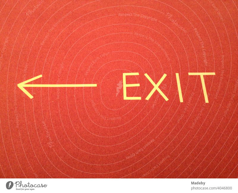 EXIT sign with yellow arrow made of tape on red carpet in a museum during the Corona Pandemic in the capital Berlin in Germany exit Arrow Clue writing