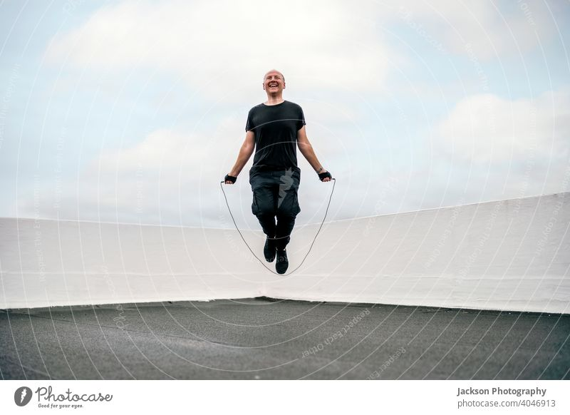 A man exercising on the rooftop using jumping rope during the lockdown sport pandemic skipping rope cardio endurance copy space outdoors person active activity