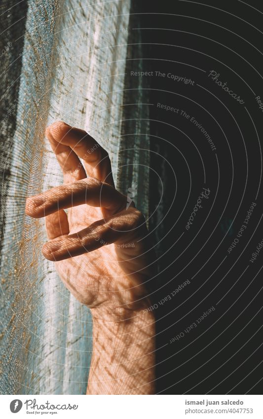 man hand gesturing in the shadows light sunlight silhouette fingers palm body part wrist arm skin person gesture concept symbol minimal minimalism background