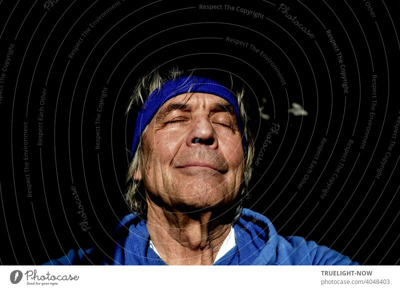 Senior, who hasn't been able to visit his barber shop in a while thanks to pandemic rules, lets the spring sun caress him, closes his eyes in a dream, and takes a selfie in a blue hoodie and headband.