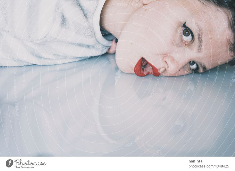 Portrait of a young woman leaning her face against a cold glass table depression blue sad mental health psychology sadness depressive white reflection mirror