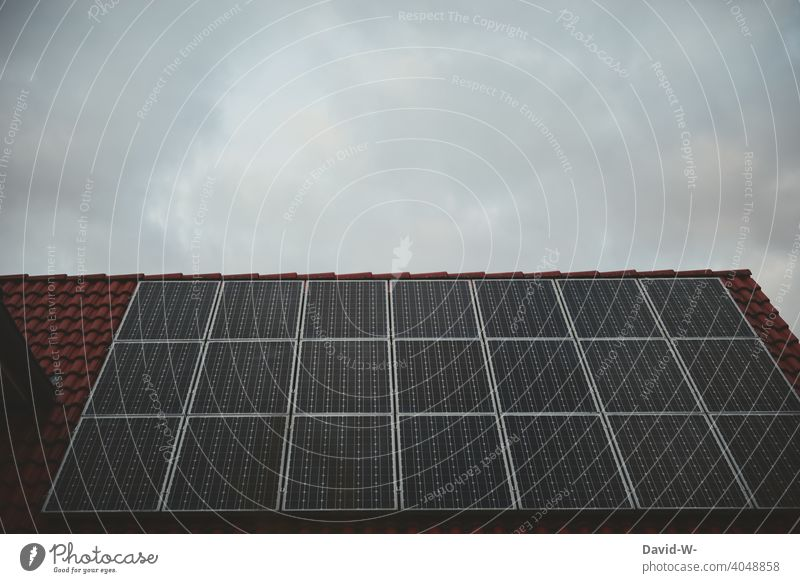 Solar cells on a roof under an overcast sky photovoltaics photovoltaic system Gray somber Bad weather Roof Covered Weather Clouds Solar Energy Renewable energy