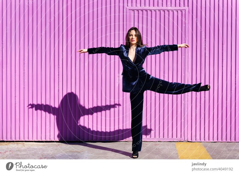 Woman wearing blue suit dancing near pink shutter. woman girl arms leg person fashion model lifestyle female urban background lady one elegant building blind