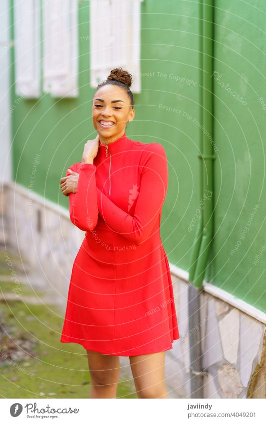 Happy black woman in red dress in front of a green wall smile smiling bow hairstyle model beauty fashion pretty portrait girl happiness young female person lady