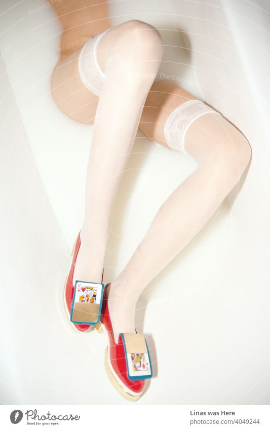 These shoes were definitely not made for walking in the fields. Why not try a milky bath instead. A photo of stylish, golden, red, avant-garde women's shoes in a milk bath. Oh, and you can see long and gorgeous legs in it as well.