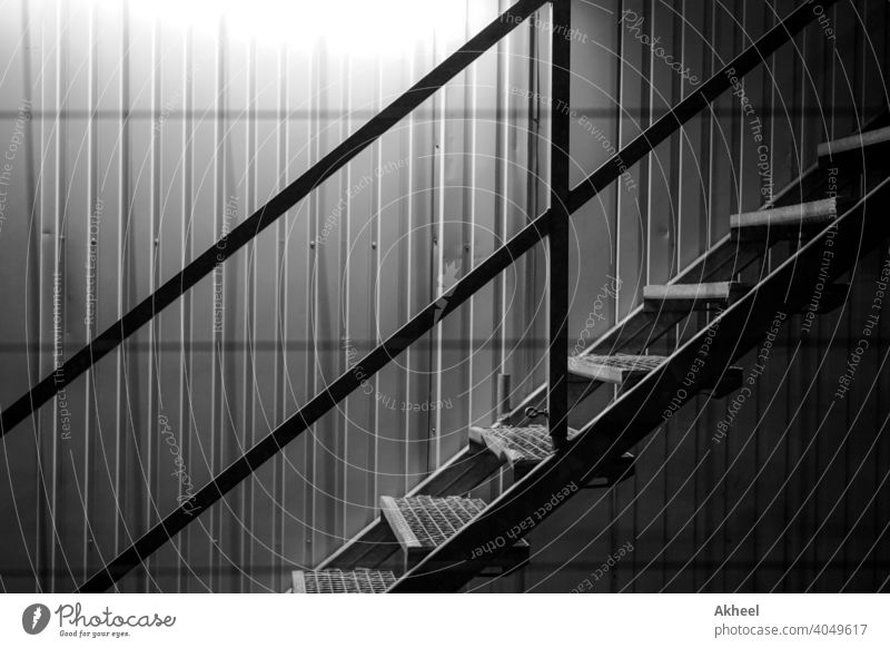 Staircase with lit background in a construction site. shipping container with stairs. abstract architectural architecture black and white building city