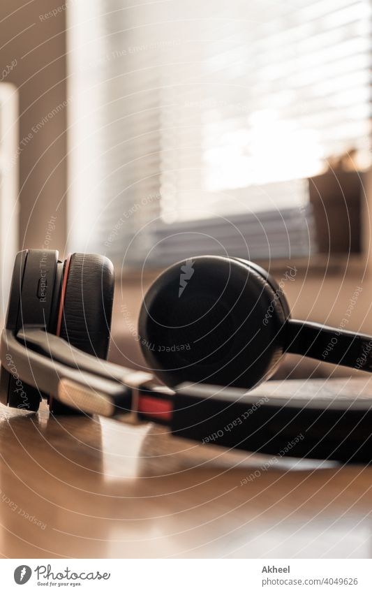 Headphones with mic resting on the table, enjoying summer day without work agenda audio background black blur business chair chairman closeup company concept