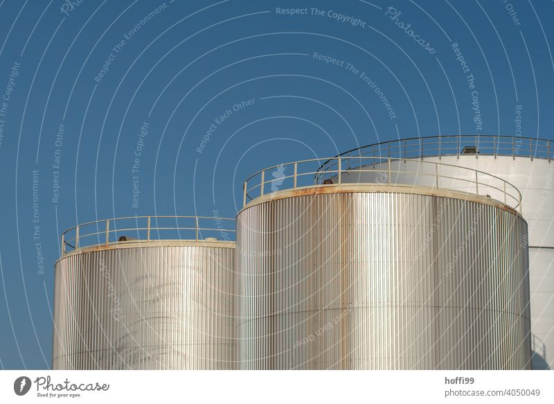 Oil tanks in harbour in front of blue sky Tank Energy industry Gas tank Gasometer Industrial plant Storage Raw materials and fuels Technology Industry Supply