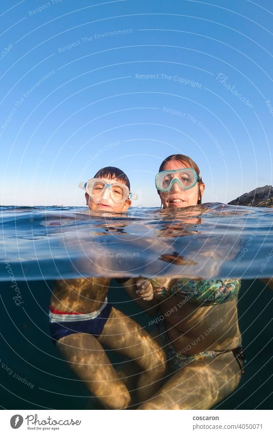 Mother and son snorkeling on a clear water beach blue boy cheerful child childhood diver diving equipment face family female fun half kid leisure little mask