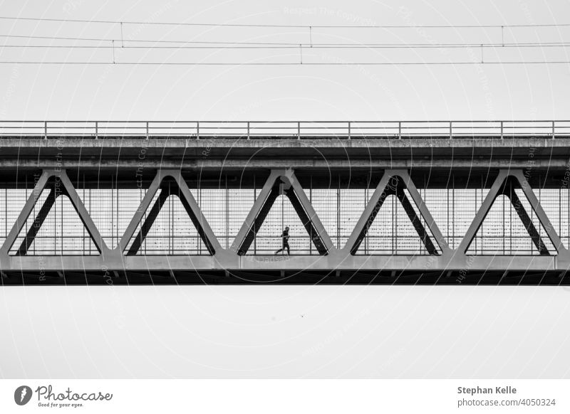 A man is jogging at the metal contrction of an iron bridge sport healthy athlete architecture design frame construction silhouette person fitness vintage