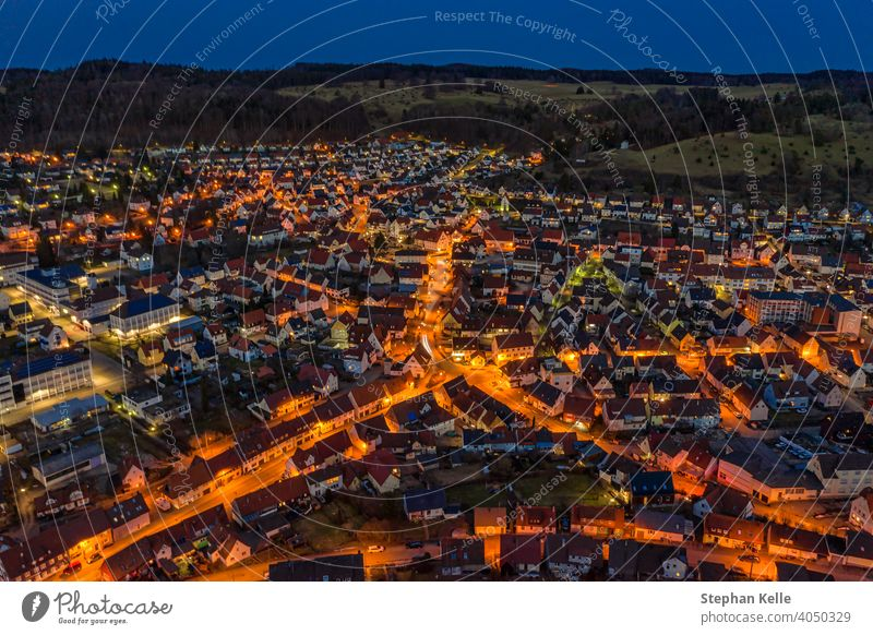 Aerial view over an illuminated city with cars at the streets and orange lights of lanterns and a hill behind the little town. night aerial urban background