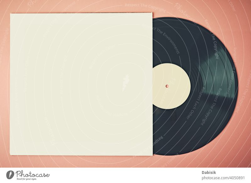 Old retro vinyl disc in paper case on pink background, mockup. Vintage toned photo record music vintage audio entertainment sound old stereo melody disk black