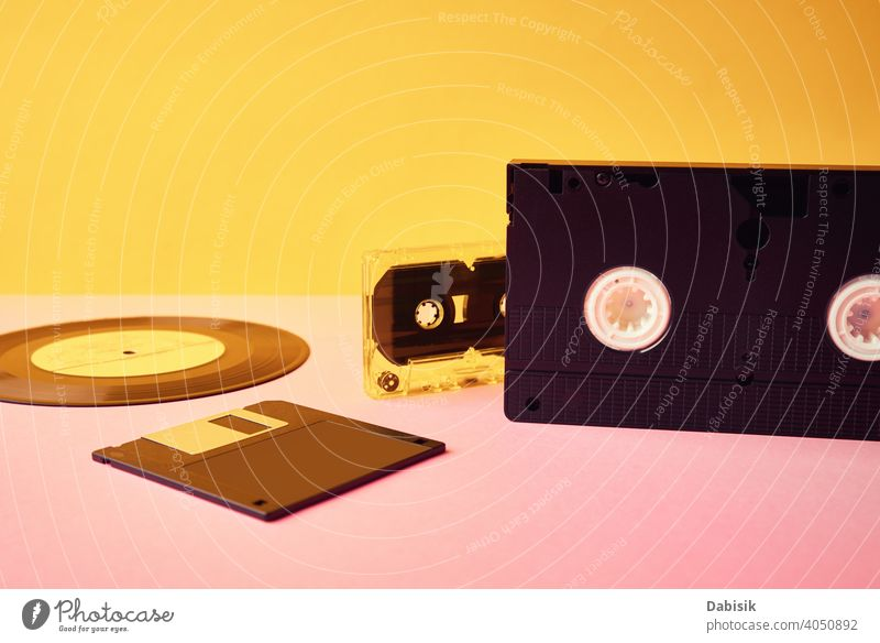 Vinyl disc, floppy diskette, vhs and tape cassete on yellow background. Retro and nostalgia concept retro cassette vinyl record vintage music audio