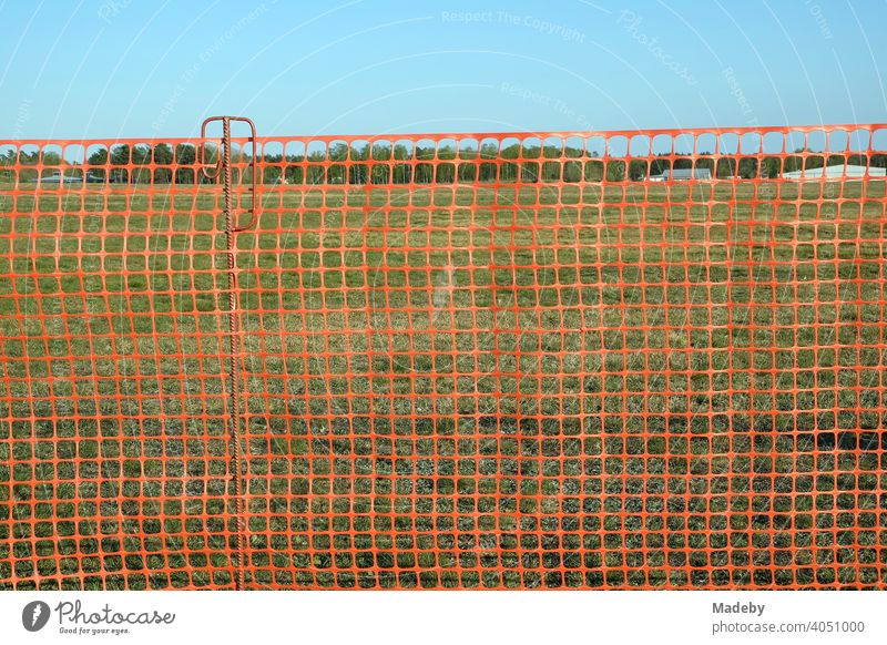 Red net made of plastic as a fence to protect the visitors at the glider airfield Oerlinghausen near Bielefeld in the Teutoburg Forest in East Westphalia-Lippe