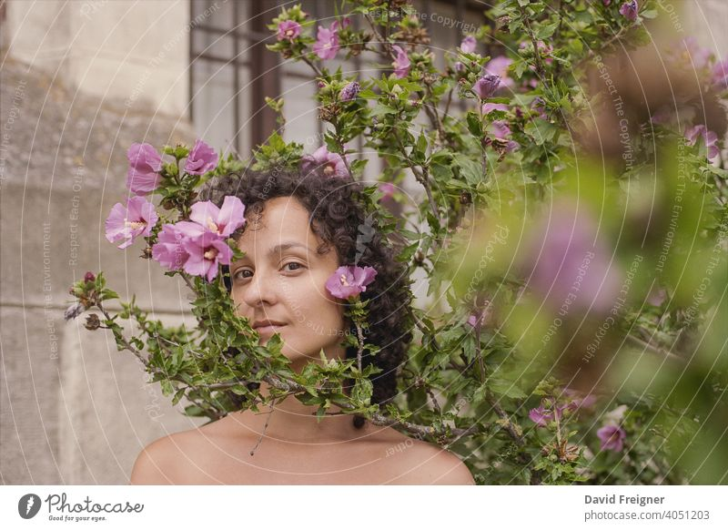 Beauty headshot of a young brunette woman with pink flowers outdoors. Shot on 35mm analog cine film. posing model person beautiful beauty fresh care skincare