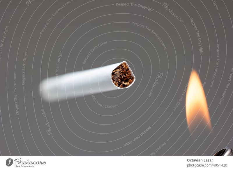Single white unlit cigarette close up macro studio shot and lighter flame isolated on gray background shallow depth of field light up open expensive smoking