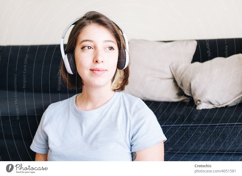 Smiling girl looking thoughtful while listening to music person woman female teenage pensive smile young happy joy smiling caucasian indoor one pretty