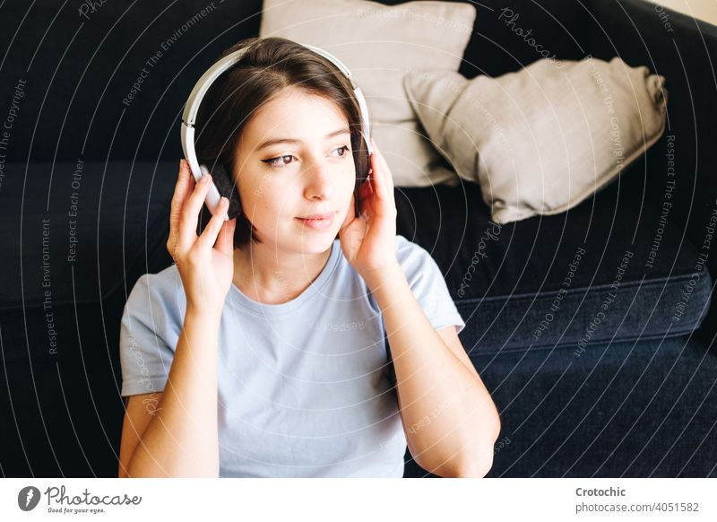 Girl with headphones at home person female woman music happy listening indoors wireless computer laptop young relaxing student enjoying relaxation smile