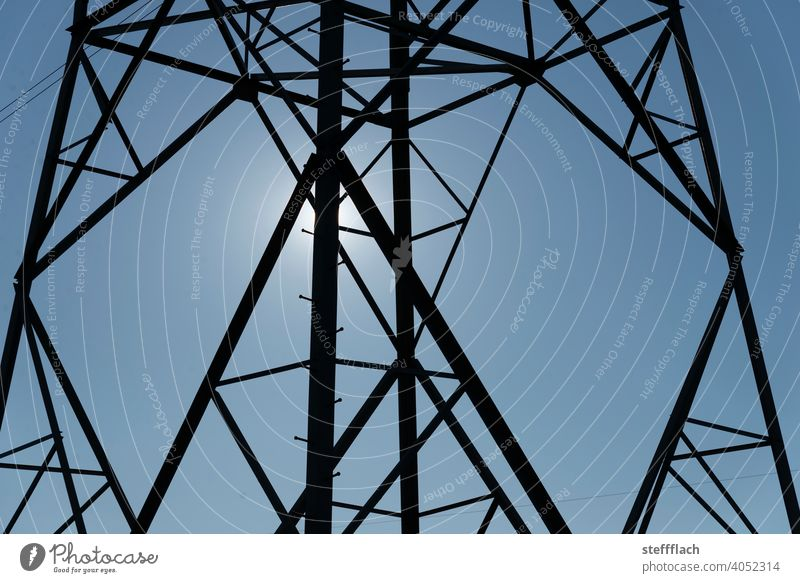 overhead line high voltage power pole lattice tower in front of blue sky Electricity pylon stream High voltage power line high-voltage cables