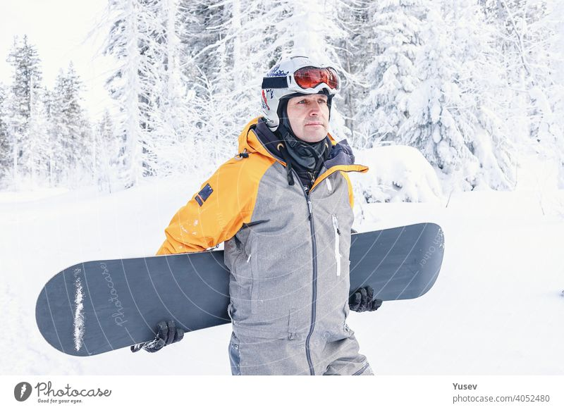 Beautiful caucasian man in a bright yellow and grey jumpsuit, white helmet and goggles is holding his snowboard. Winter sports, leisure activity. Vacation in the mountains. Front view.
