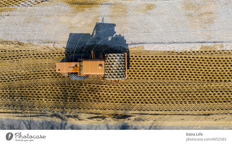 Aerial view on road roller with spikes is working at construction site, compacting base for asphalt road Above Asphalt Base Building Site Civil Engineering