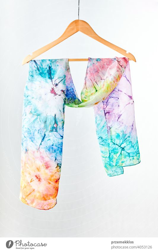 Silk colourful hand painted tied scarf put on white background. Woman fashion, tying a scarf, wearing a scarves. Stylish ways to tie and wear scarves shawl