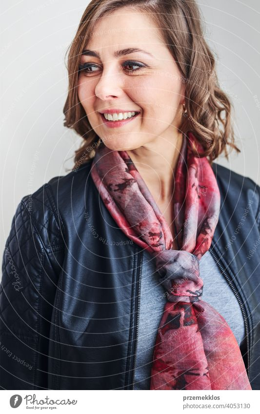 Young beautiful smiling woman wearing silk scarf around her neck and leather jacket looking away standing at plain background person model portrait beauty style