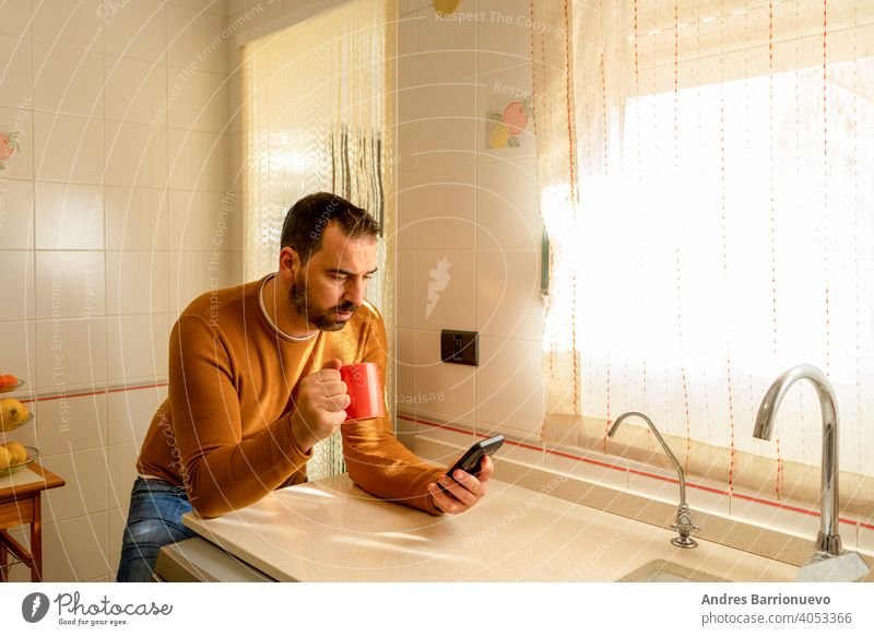 Handsome bearded man in an orange sweater looking at the smartphone in the kitchen while having a cup of coffee mobile phone communication guy drink positive