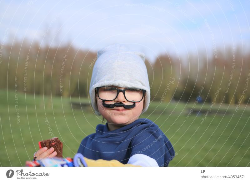 small child wearing glsses, a hat and a fake moustache Looking Portrait photograph Multicoloured Mysterious Emotions Funny Moustache Fashion Face