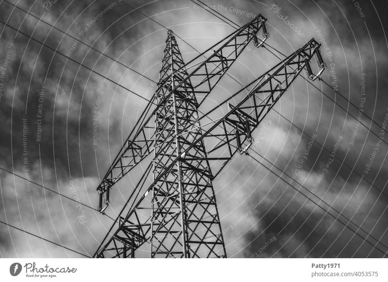 Electric pylon in front of dramatic cloudy sky b/w photo Electricity pylon Energy industry Sky Cable Industry High voltage power line Technology