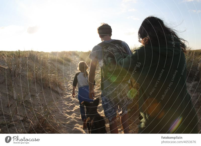 Man, woman and child with dog on the way over the dune to the beach Vacation & Travel family vacation Together Woman Child Relaxation Sand Family time time-out