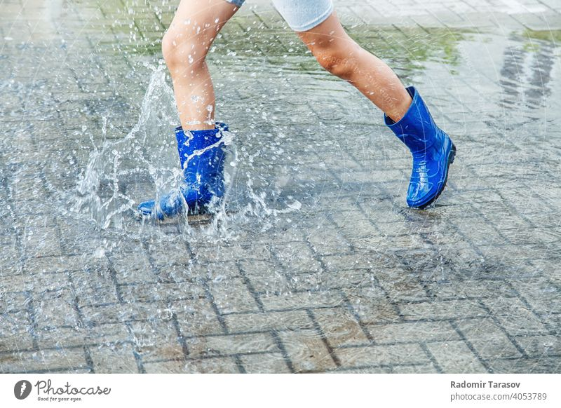 girl in blue rubber boots jumping in a puddle after a rain autumn water season wet weather walk fun child outdoors legs street nature young wearing people