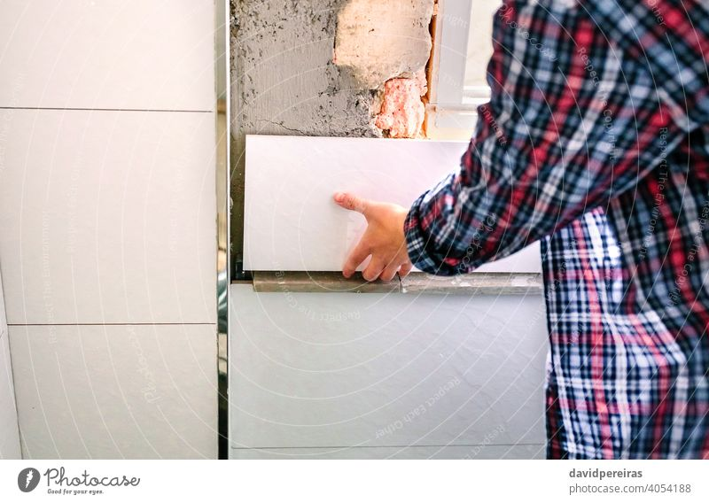 Unrecognizable female bricklayer laying tile on the wall unrecognizable placing bathroom reform copy space position adjusting mason detail hand woman piece