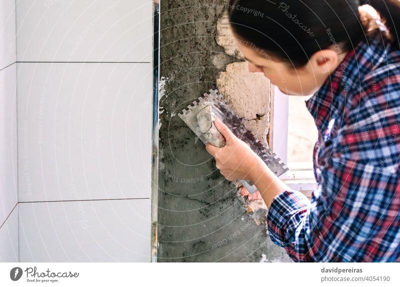 Female bricklayer leveling cement with a trowel unrecognizable woman concrete tile bathroom masonry copy space closeup construction female tiled spread
